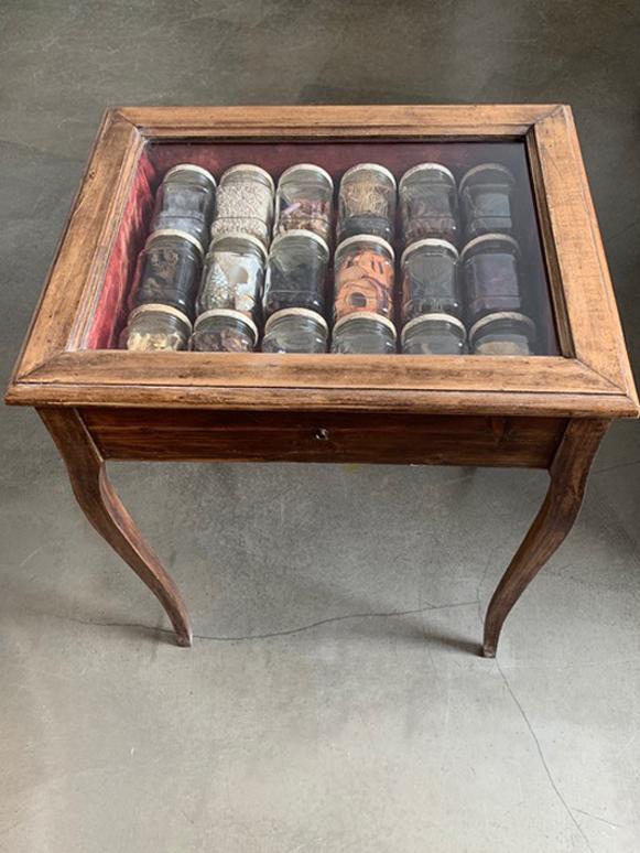 """Nathalie Giraud, Duftsammlung """"Mélancolie"""", 2021, 18 verschlossene Gläser mit organischen Stoffen, Deckel mit Buchseiten kaschiert, in antiquarischer Standvitrine, je 11,5 x Ø 7 cm (Gläser), in 76 x 57 x 45 cm (Standvitrine)"""