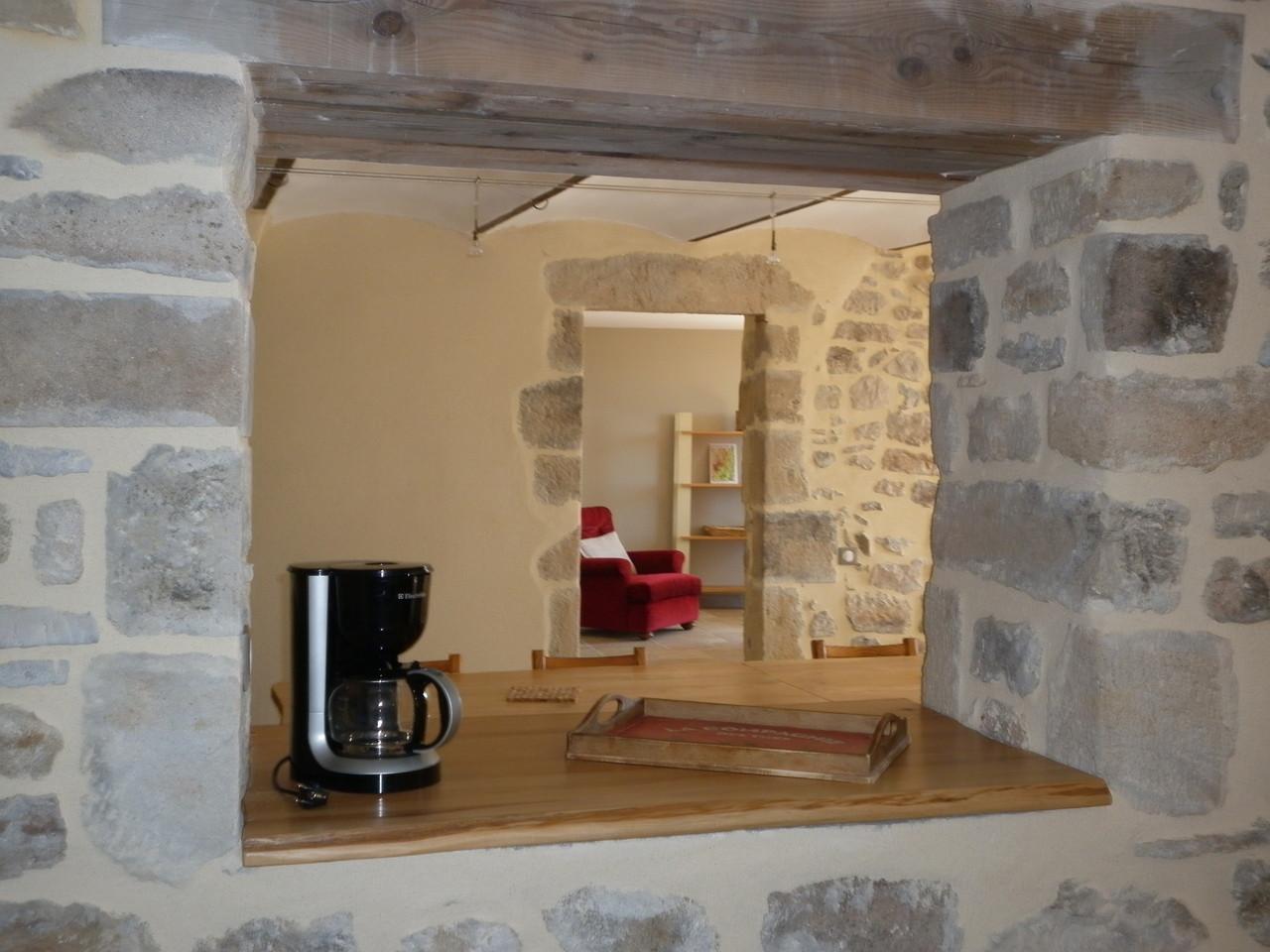 vue sur salle à manger et salon depuis le passe-plat de la cuisine du gîte de Coustillou