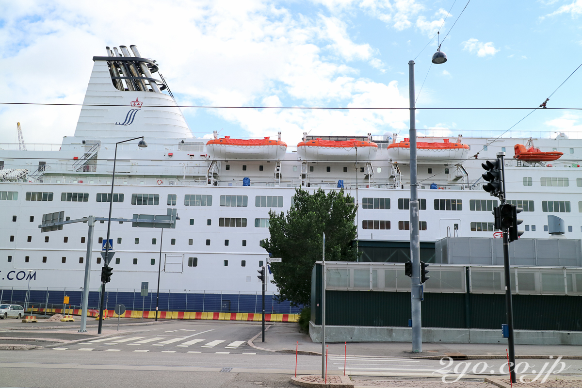 陸地を走る車や歩行者の後ろに巨大な船が見える。