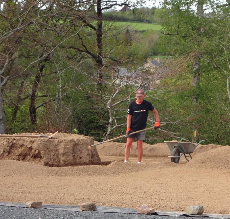 Jean Claude Blanchet prépare la terre pour faire une pelouse ; ça fait de la poussière.