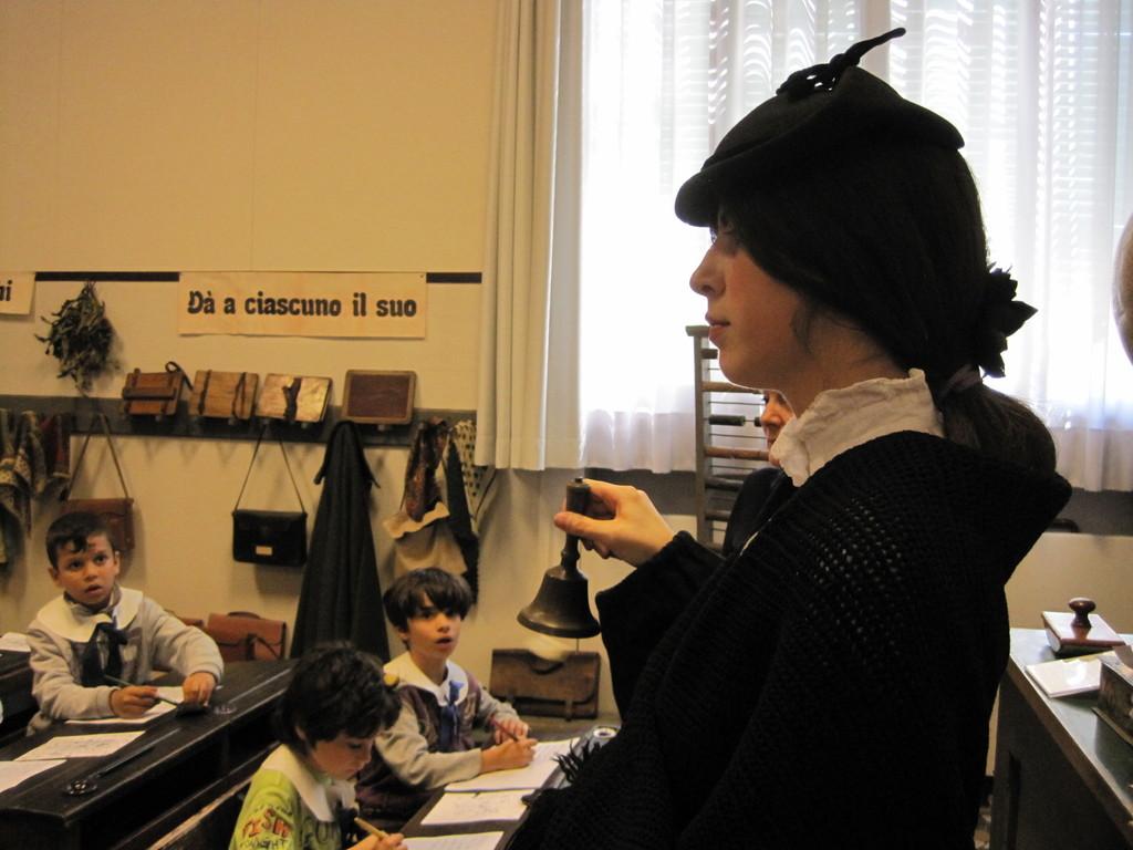La maestra severa suona la campanella della ricreazione.
