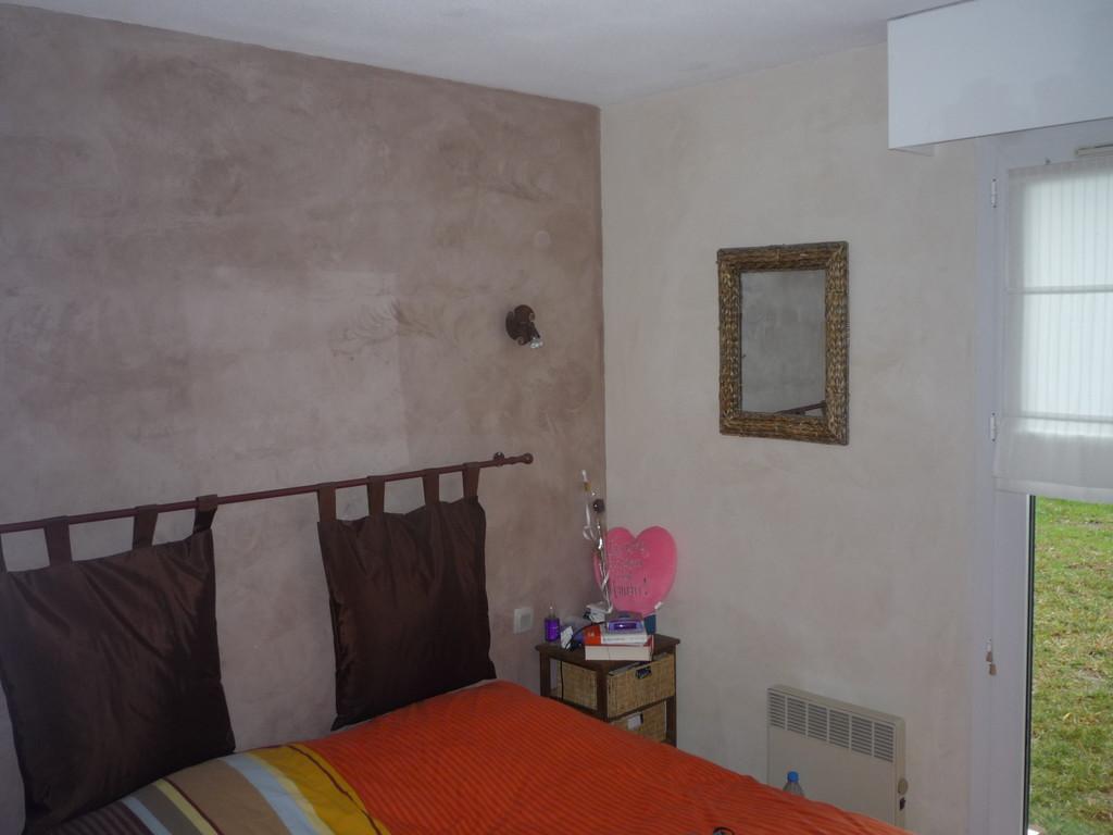 Cire bordeaux et cire ivoire sur mur crépi