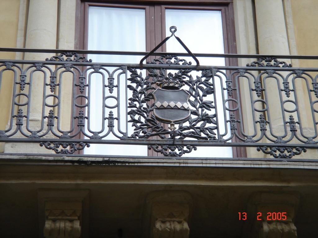Il balcone centrale. Particolare dello stemma nobiliare stemma dei Cirino (Cinque losanghe su fondo dorato corona di baroni e croce di cavalieri di Malta).