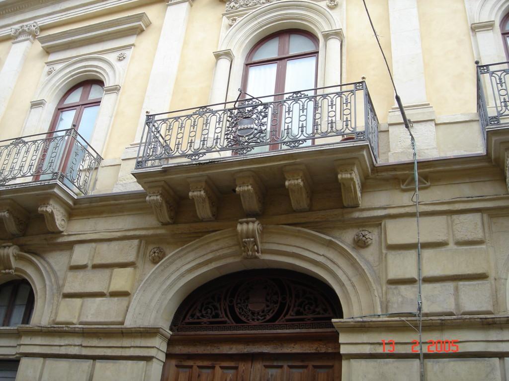 Il balcone centrale del piano nobile di Palazzo Cirino che sormonta il portale. Con stemma del casato
