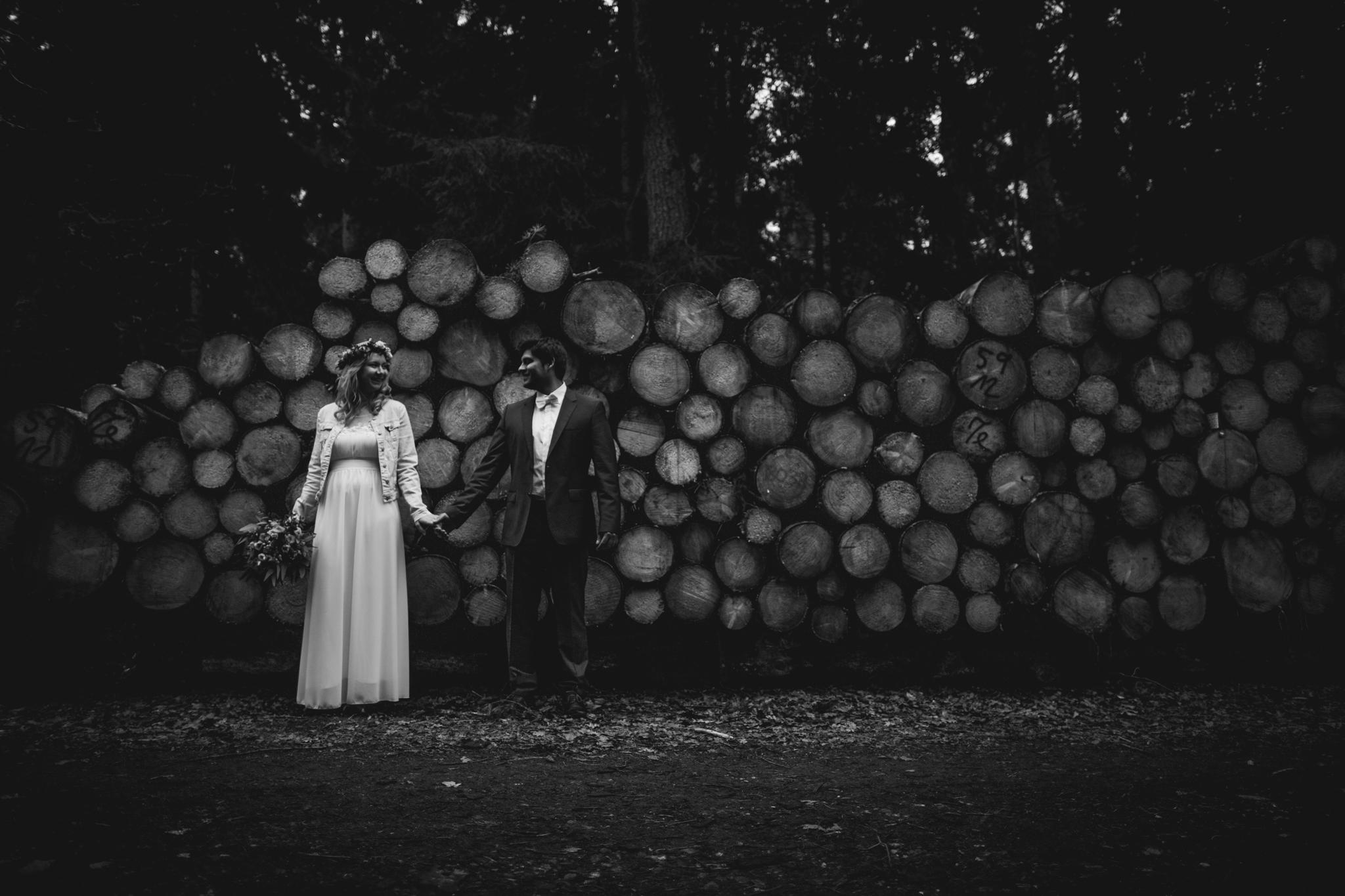 Hochzeitspaar im Wald vor Holz