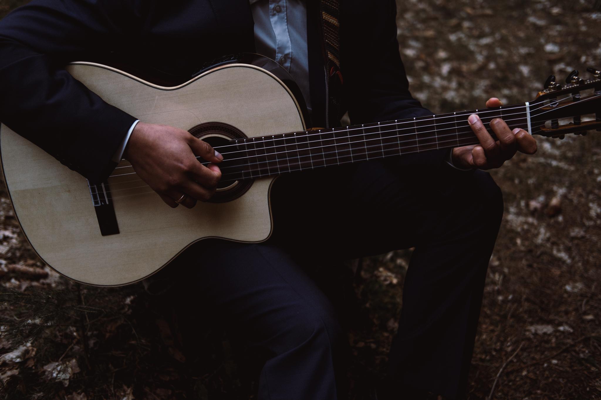 Bräutigam spielt Gitarre im Wald