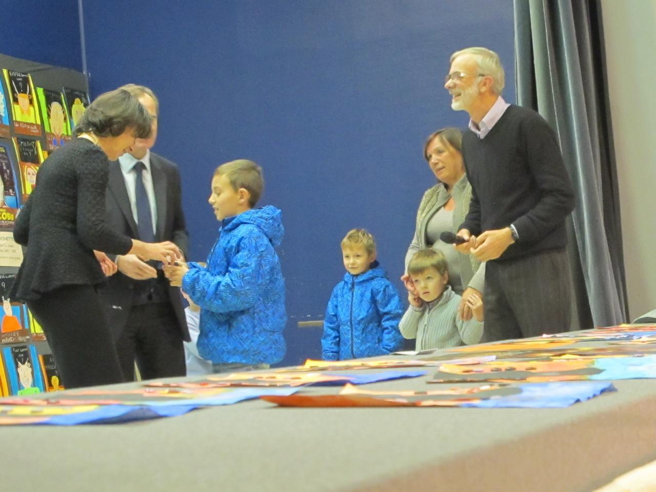 Monsieur le député a demandé à un enfant de remettre la médaille de l'Assemblée Nationale à Madame Lalonde
