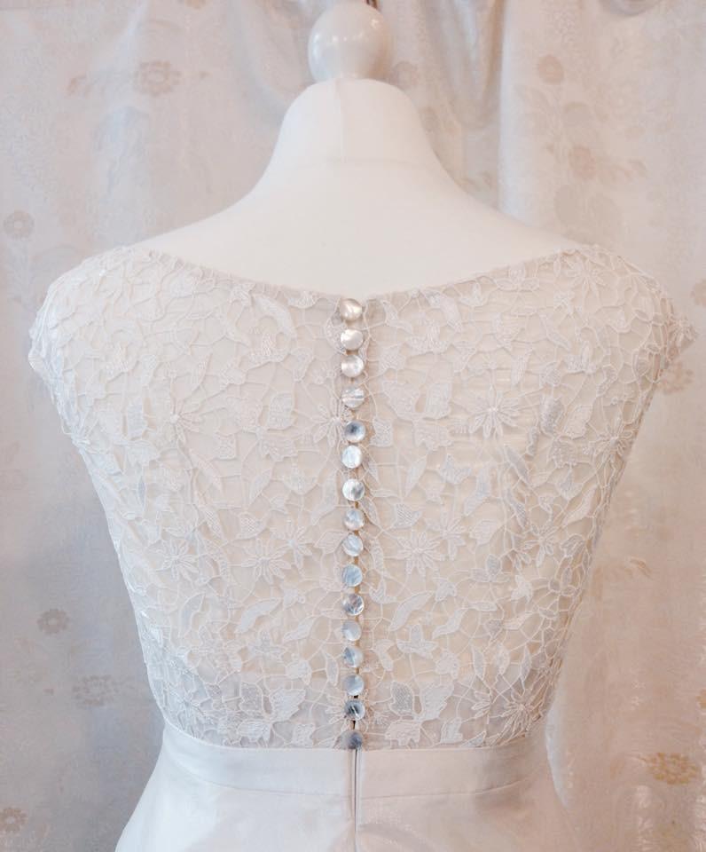 Brautkleid aus Seidenorganza und Guipure-Spitze mit Perlmuttknöpfen