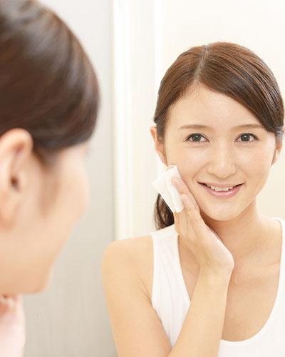 鏡の前に立ち笑顔で肌のお手入れをする女性