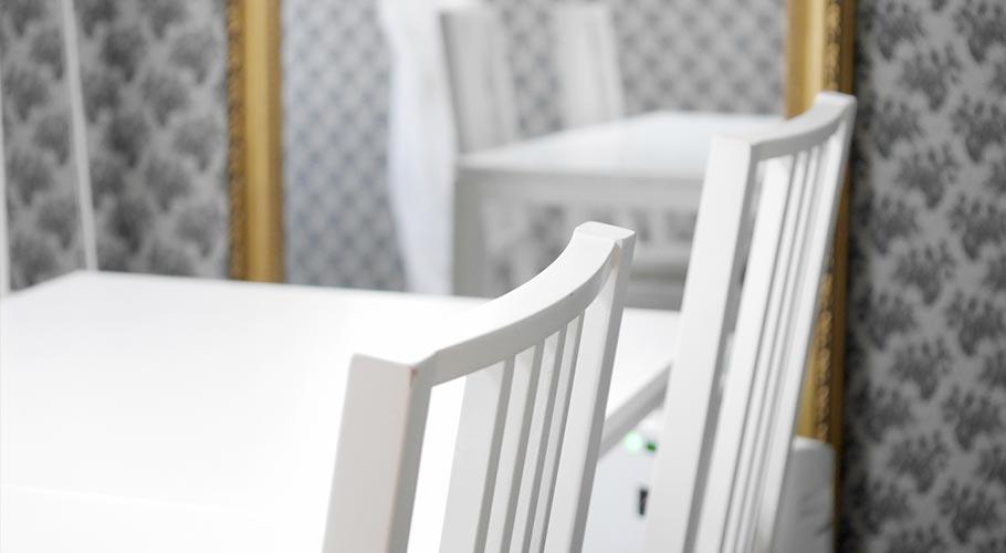真っ白いテーブルと椅子、大きな鏡のある落ち着いたサロンの風景