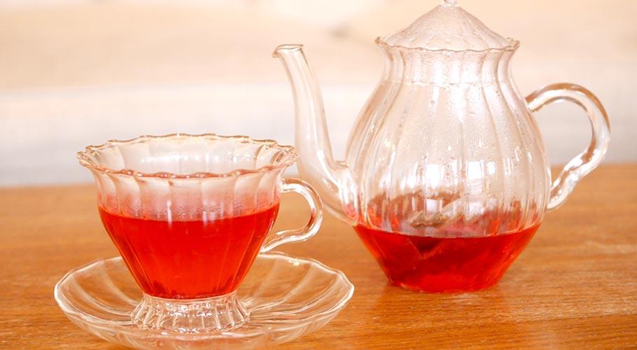 テーブルの上に置かれたガラス製の紅茶ティーポットとカップ