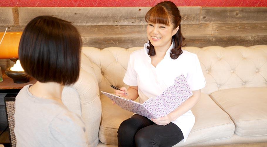お客様と向き合い笑顔で施術後のアドバイスをするサロンオーナー もとがや真理子