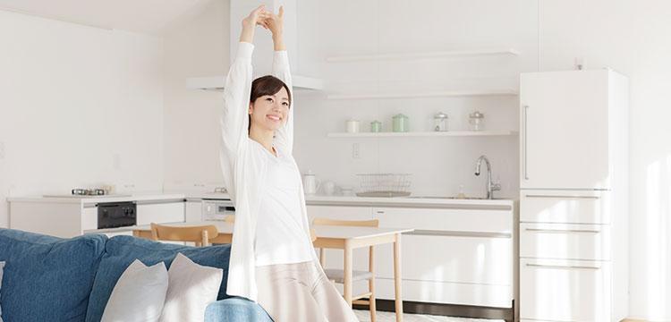 朝のリビングで目覚めが良くスッキリした気分で窓に向かって背伸びする女性