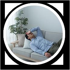 不眠に悩み疲れ切ってソファに寝転がる男性