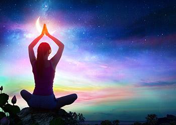 チャクラのイメージでスピチュアルな瞑想をする女性