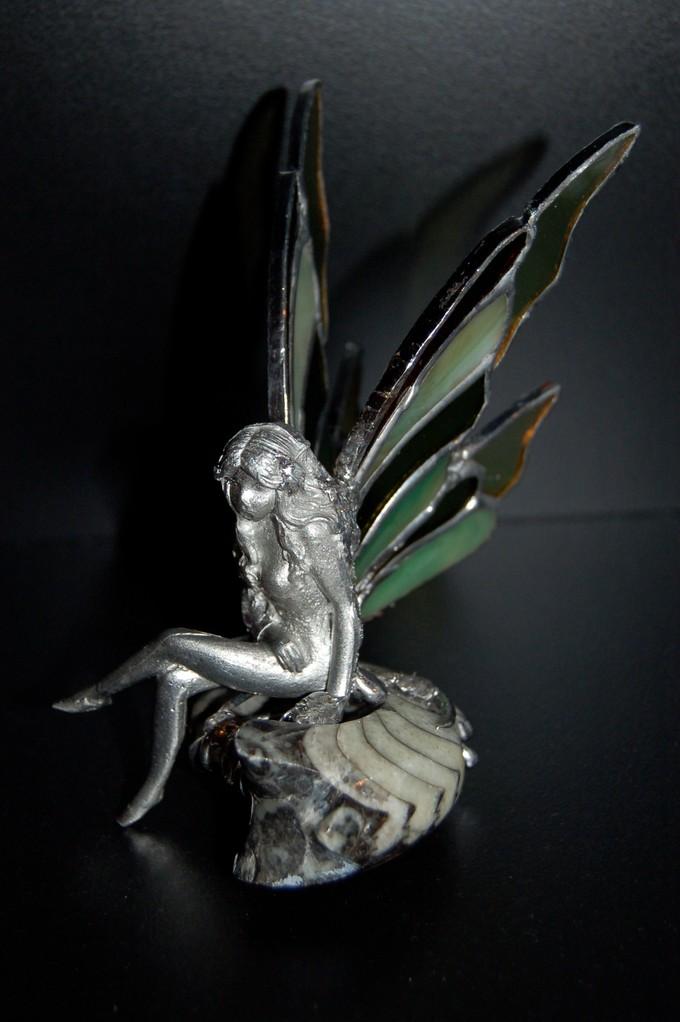 Elfe: statuette en étain avec ailes en verre posée sur fossile