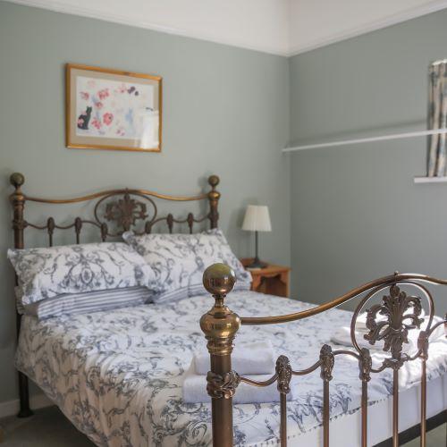 The main bedroom has a splendid brass bedstead