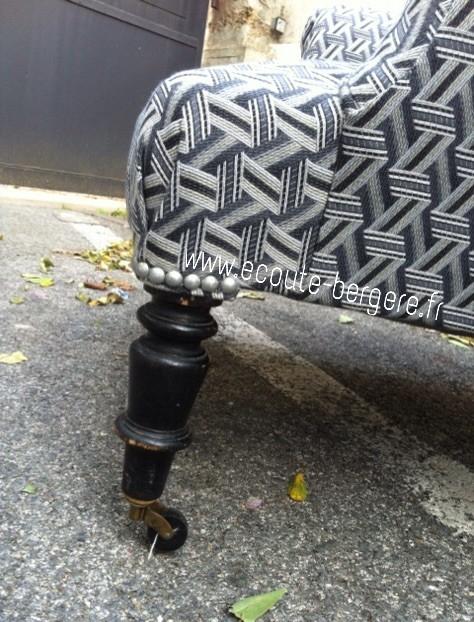 Zoom sur le pied avant d'un fauteuil anglais, recouvert de tissu Lelièvre, fini par un pli en V maintenu par quelques clous coloris niquel mat au dessus du pied Napoléon 3