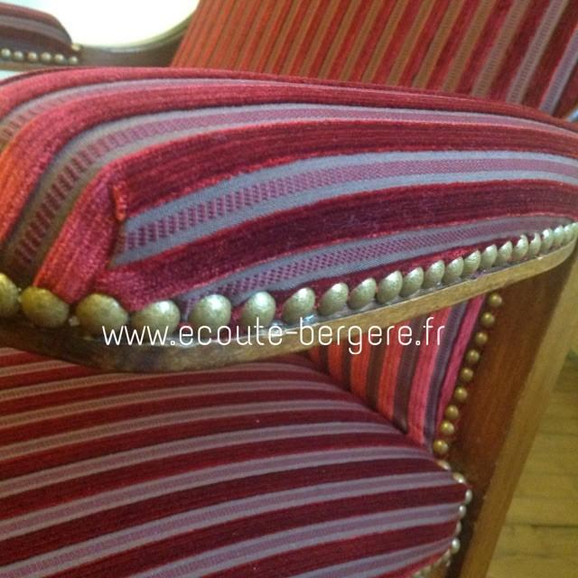 Gros plan sur un fauteuil Voltaire recouvert de tissu Lelièvre en velours rouge à rayures, fini par des clous dorés classiques de chez Houlès