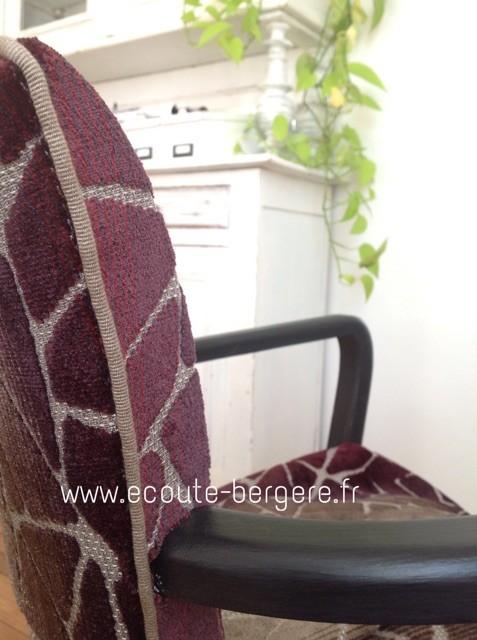 Détail de la finition d'un fauteuil Bridge patiné noir mat, recouvert de tissu en velours aubergine dégradé: un passepoil beige de chez Houlès orne l'arête du fauteuil.