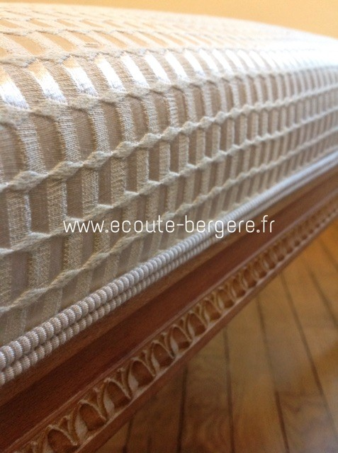 gros plan sur une passementerie type double-corde de chez Houlès, écrue, assortie à un tissu faux uni texturé géométrique mat et brillant de chez Lelièvre, sur un banc de style Louis XVI Jacob.