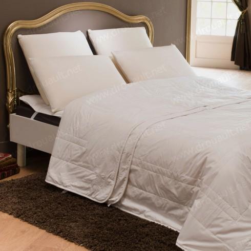 Un lit équipé d'oreillers et couettes pure plumes et duvets par Ecoute Bergère tapissier