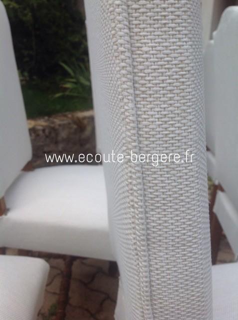 Zoom sur la finition d'une chaise Louis XIII rénovée dans un tissu blanc à grosse trame: l'arête du dossier est soulignée par un passepoil cousu dans le même tissu