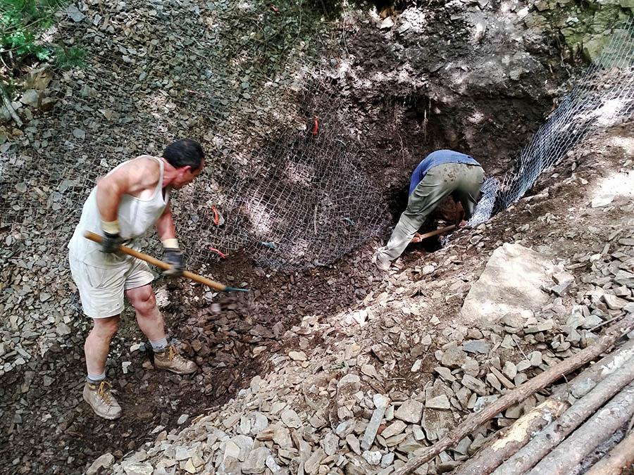 Travail de réouverture d'une entrée de galerie obstruée par les cailloutis de solifluxion près de Vialas (48)