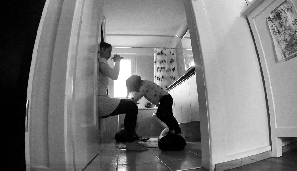 Yogamami mit Yogakid und Yogababy im Badezimmer beim Zähneputzen. Yogamami trainiert ein wenig die Beine und Yogakid balanciert auf der Rolle, wärend Yogababy sich im Sitzen übt.