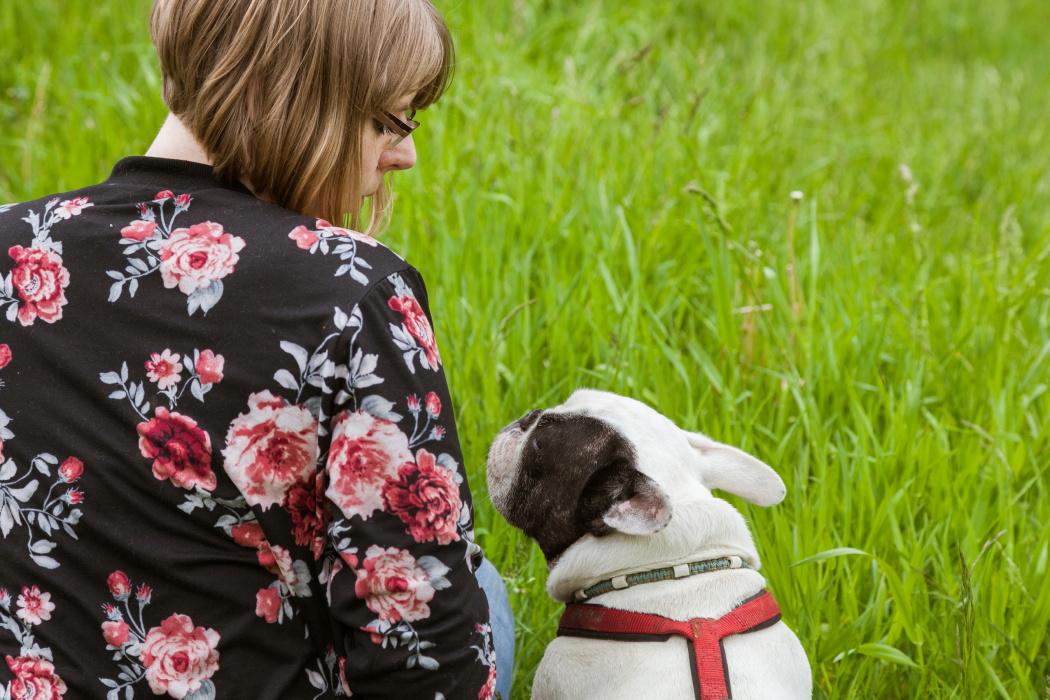 Hundetrainerin Rebecca sitzt neben einem kleinen Hund auf einer Wiese