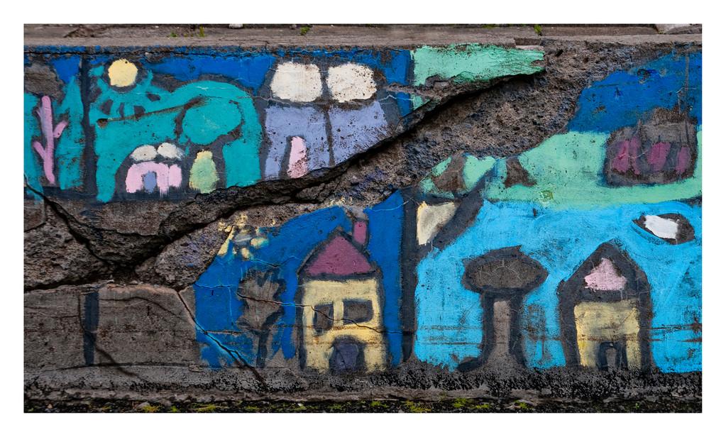 Kleiner Teil einer bemalten Mauer, die zu einem Schulgebäude eines kleinen Ortes gehörte