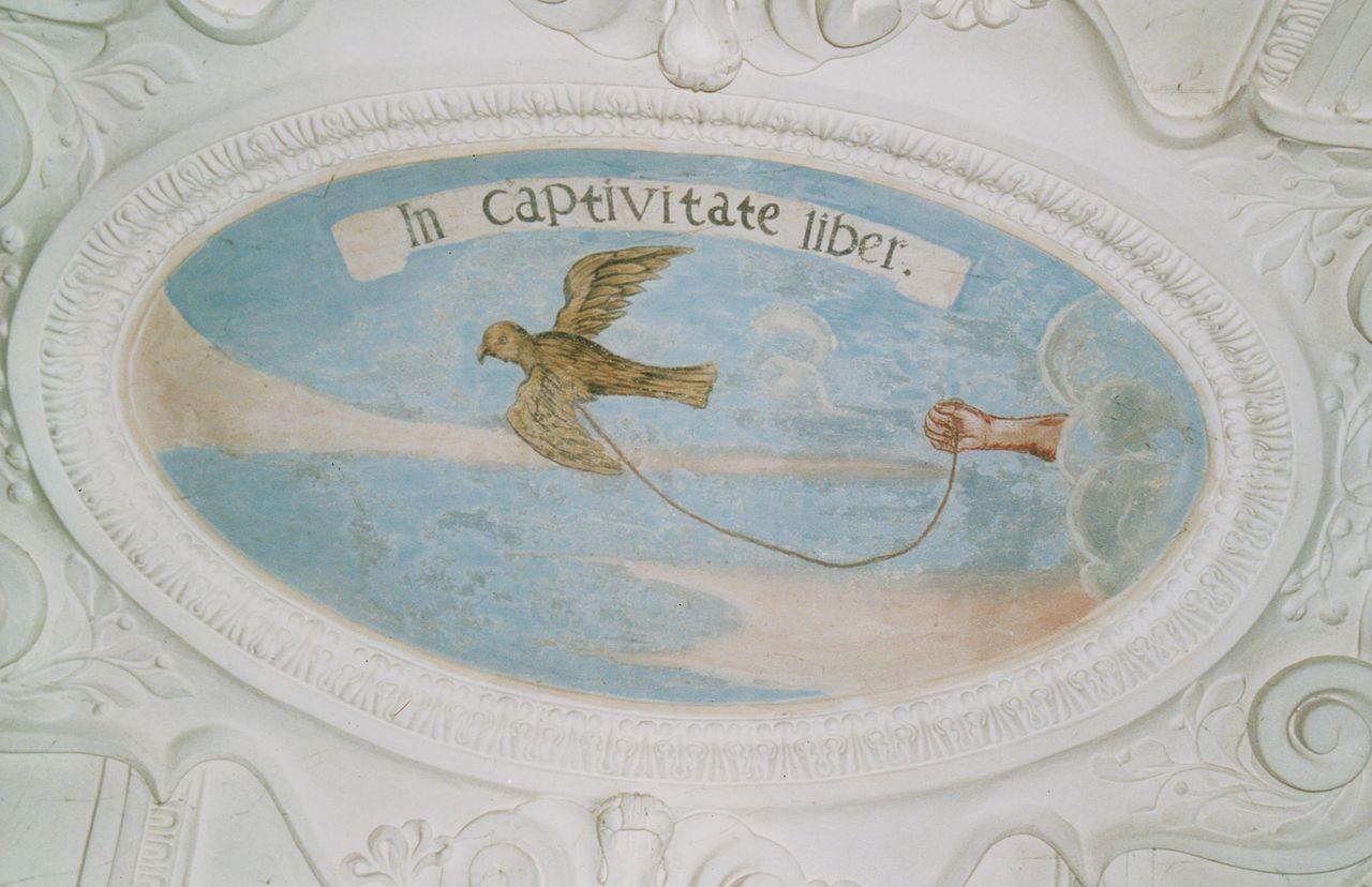 """8) Wir sehen einen Vogel, der von einer Hand locker mit einer Schnur gehalten wird: """"IN CAPTIVATE LIBER"""" (In Gefangenschaft frei)."""