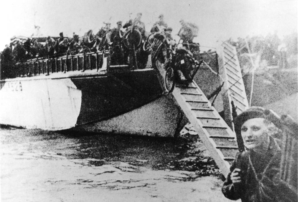 Invasion 1944: Commandosoldaten mit Fahrrädern gehen vom Landungsboot. Im Vordergrund: Corporal Sayers vom 3. Trupp