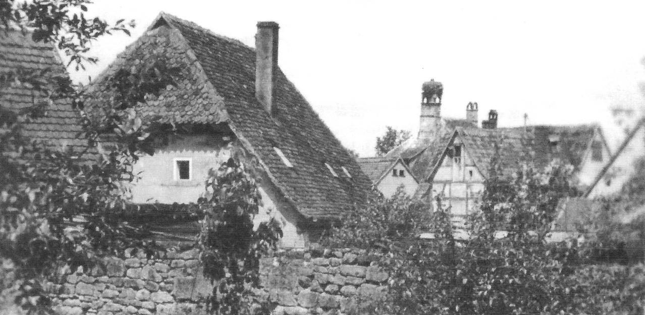 """Links das Hirtenhaus: Ältestes erhaltenes Profangebäude Brucks. Im Hintergrund die """"Dachlandschaft"""" des Schlösschens."""