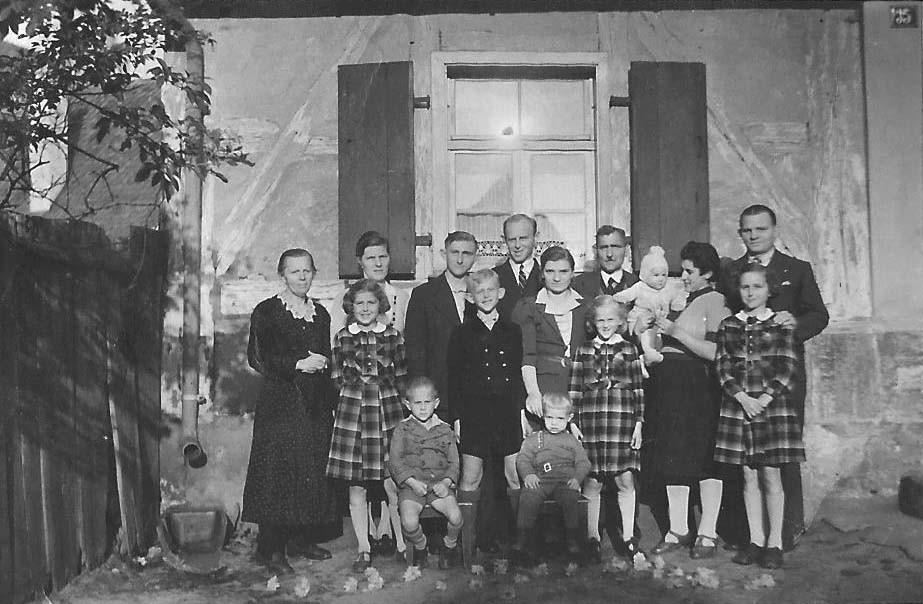 Oma und Oda Geißer mit ihren Kindern und deren Ehepartnern und den Enkelkindern vor dem Hirtenhaus
