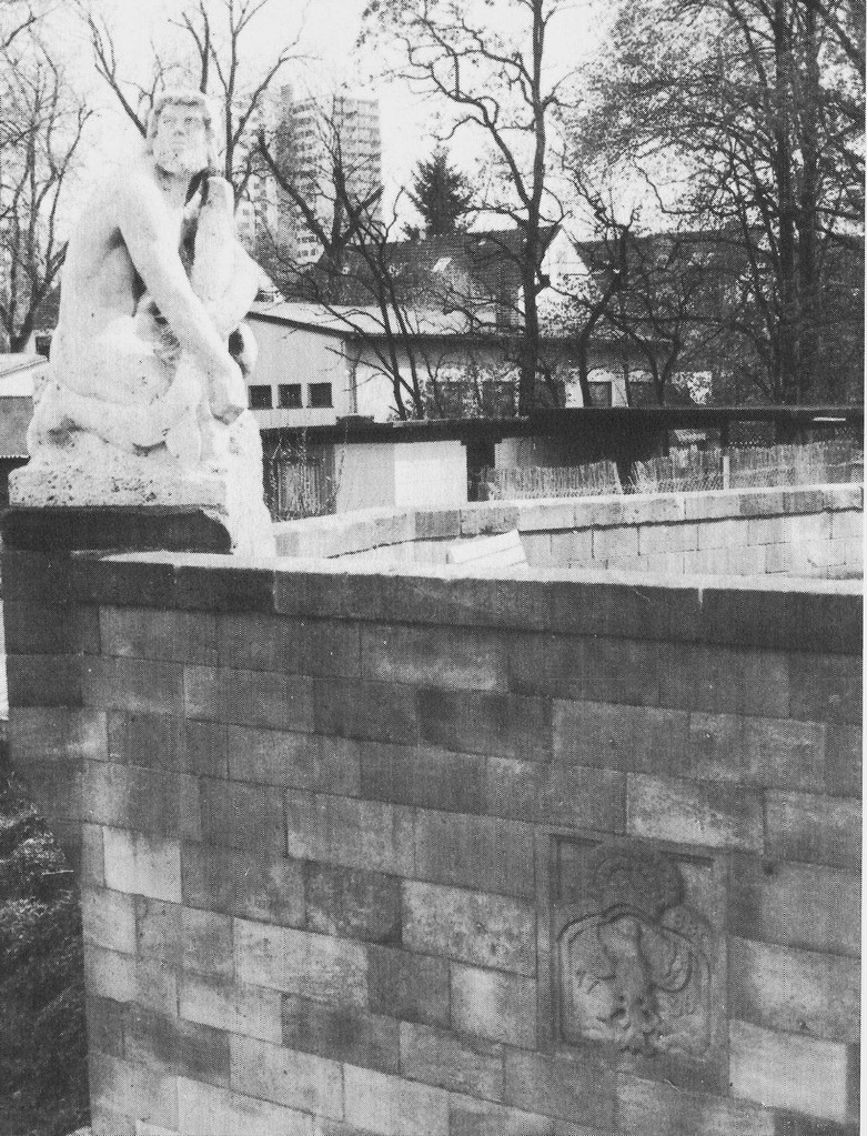 """Nordseite der nach dem Krieg erbauten modernen Brücke, östlicher Brückenkopf: Skulptur """"Fischer"""" von E. Hoffmann, eingebauter Wappenstein FMZBB 1736 (Friedrich Markgraf zu Brandenburg-Bayreuth)"""