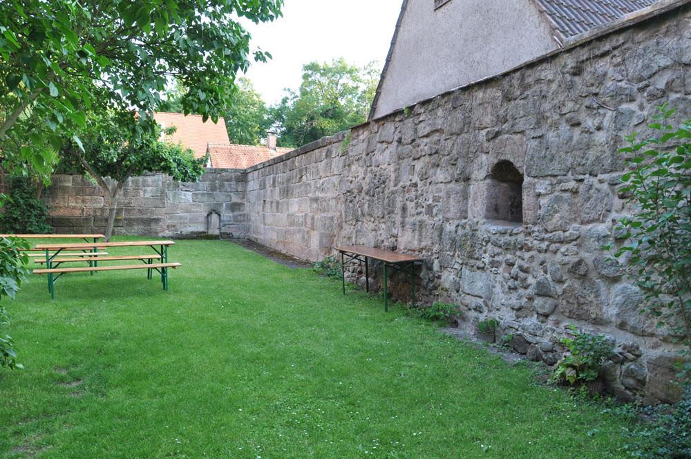 Reststück der alten Friedhofs-/Wehrmauer, rechts im Bild