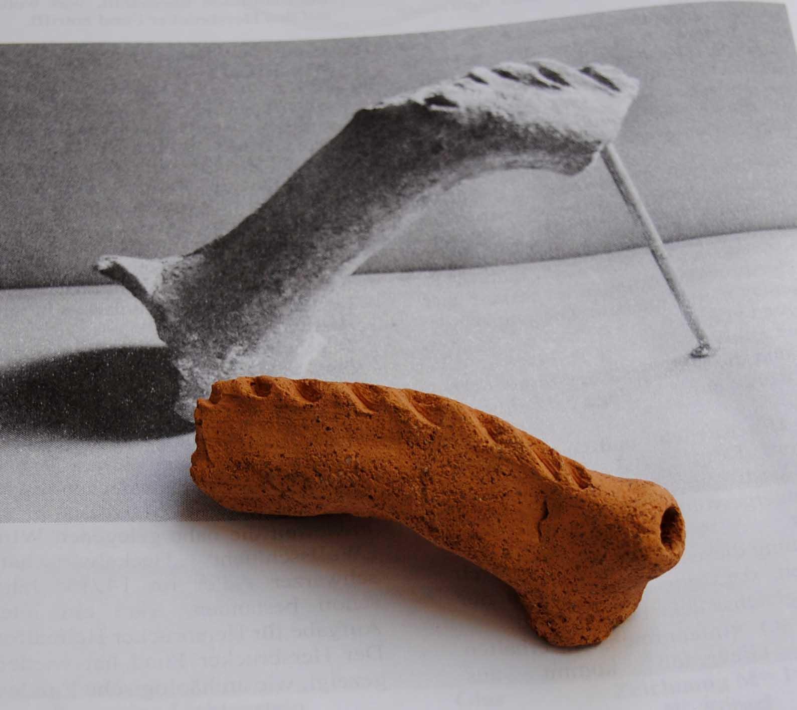 Griffstück-Fragment eines mittelalterlichen Aquamanile vor abgebildetem Vergleichsstück