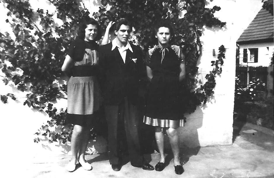 """An der """"Fotowand"""" des elterlichen Siedlerhauses: Betty links, Mitte der Verlobte ihrer Schwester, Erwin Bitter, rechts Ottilie"""