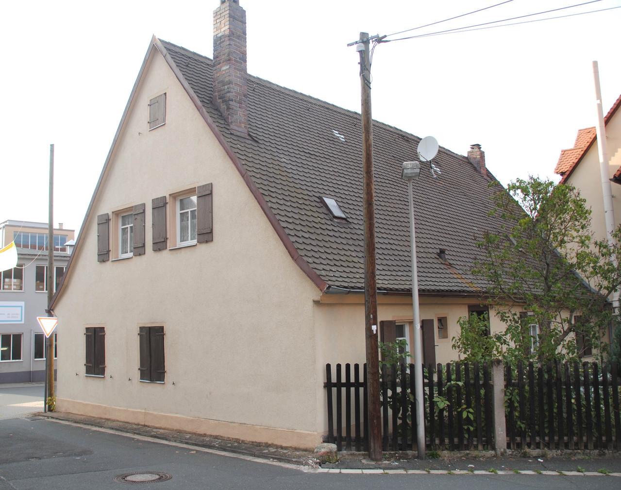 Das Häuschen heute: Einmündung der Gasse in die Hauptstraße. Links ist ein Teil der Spitzgußfabrik zu sehen.