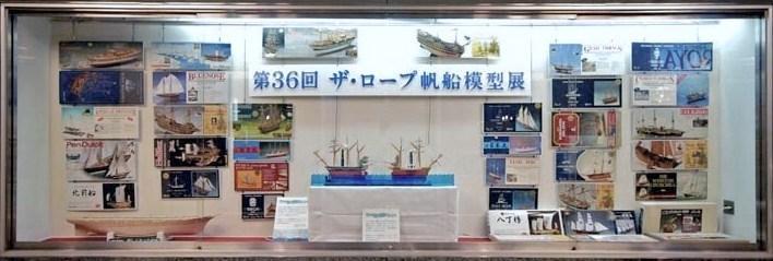 展示会場の通路側面のショーウィンドウを飾ったキットの箱絵と外輪船とスクリュウ船の綱引き動態模型。
