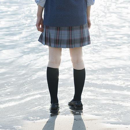海辺に佇む女子高校生の後ろ姿