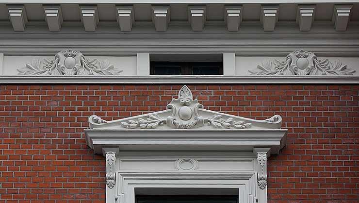 Detailausschnitt der Fensterbekrönung und Attika