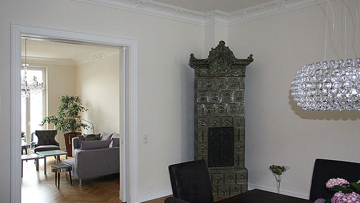 Raumaussicht vom Essbereich ins Wohnzimmer mit einem Kachelofen aus dem 19. Jahrhundert