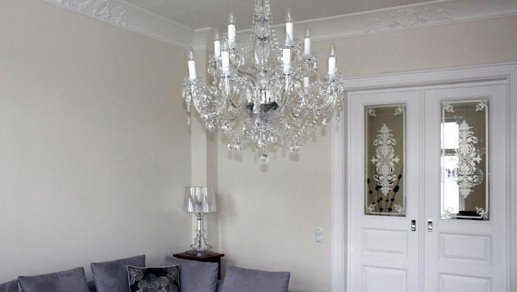 Wohnzimmer mit subtil weiß gehaltenem Leimfarbenanstrich im Bereich der Decke und des Stucks