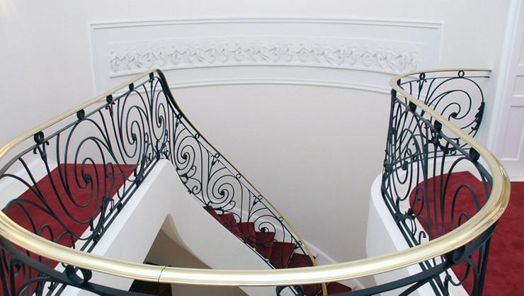 """Treppenhaus 1. OG mit Blick auf das gerahmte, antike Stuckrelief """"Die tanzenden Stunden"""""""
