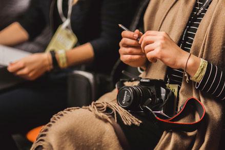 Dame mit Stift und Kamera als Symbol für Pressekonferenz
