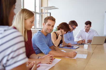 Mehrere Menschen an einem Tisch als Symbol für Schulungen