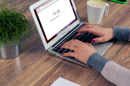 Hände auf Laptoptastatur mit Google im Display als Symbol für Suchmaschinenoptimierte Texte