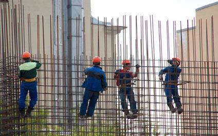 Vier Bauarbeiter, die sich an Bewehrungseisen festhalten